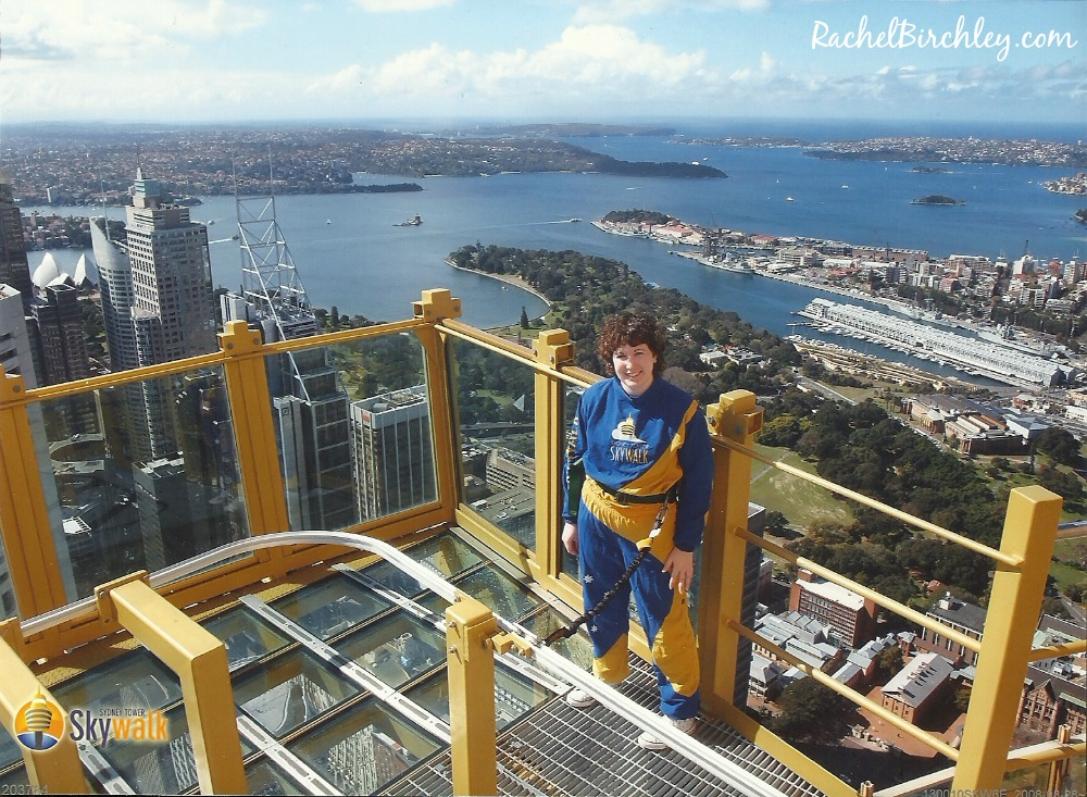 This is me on the Sydney Tower Eye Skywalk. I'm high above the city streets with Sydney harbour behind me. RachelBirchley.com