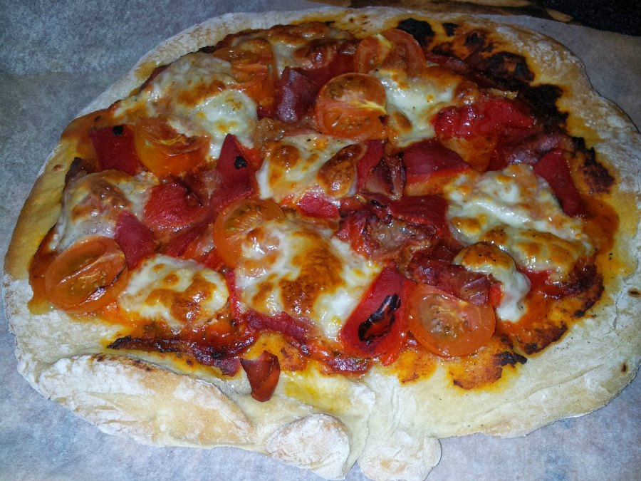 Homemade pizza with smokey paprika tomato paste, parma ham, roasted red peppers, cherry tomatos and reduced fat mozzarella.