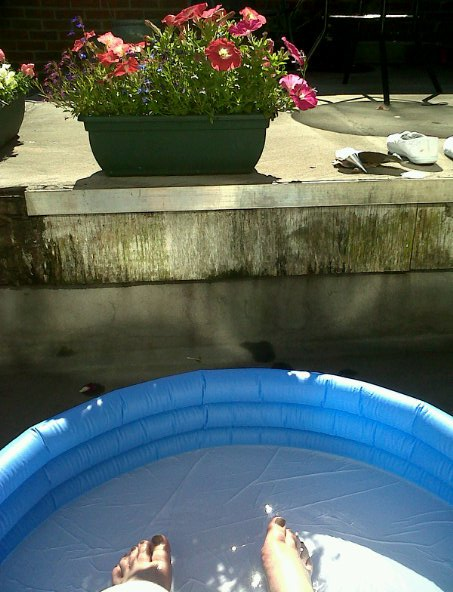 Cooling off with my feet in the paddling pool.